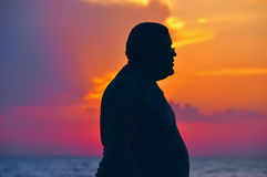 Silhouette man full. Tumny man silhouette of a man, complete with glasses on the background of sunset, dawn sea. red and orange beautiful sky at dawn. Beach and Stock Photo