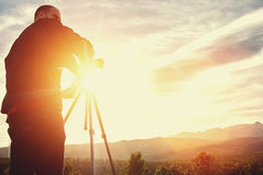 Silhouette of a man geodesist using theodolite for determines the required coordinates to construct a new building structure, royalty free stock images