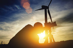 Silhouette of a man geodesist using theodolite for measures distance for bridge construction while standing against windmills and Royalty Free Stock Photos