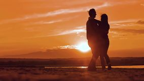Silhouette man and girl of a happy young married couple slow dancing outside at sunset. Couple enjoying on nature the