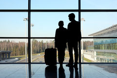 Silhouette of man and girl standing near window Stock Images