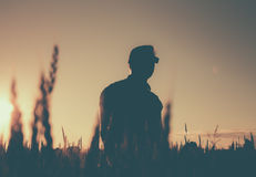 Silhouette of a man with glasses in the field on a belt. Royalty Free Stock Image