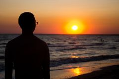 Silhouette of a man in glasses, in the rays of the setting sun near the sea. place under the text, relax on the sea. Silhouette of a young man with glasses stock photos