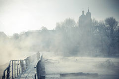 Silhouette of a man goes across the bridge over  river. Silhouette of a man who goes across the bridge over the river with condensate winter frosty morning Stock Images