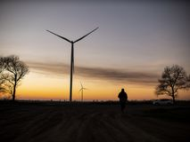 Silhouette of a man goes to sunset in the direction of wind turbines royalty free stock photos