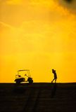 Silhouette of a man during a golf swing. Silhouette of a golf cart and a golfer swinging a club Royalty Free Stock Photography