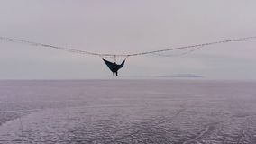 Silhouette of a man in a hammock mounted at high altitude. stock video