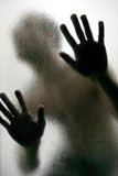 Silhouette of a man with hands on a frosted glass Stock Photos