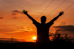 Silhouette of a man with hands raised Royalty Free Stock Photos