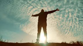 Silhouette of a man with hands raised in the sunset concept for religion, worship, prayer and praise. silhouette of a. Man at sunset nature of hand in the stock footage