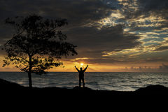Silhouette of man with hands raised Royalty Free Stock Images