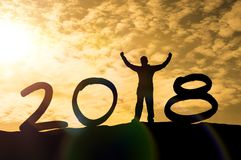 Silhouette of a man hands up on a mountain top and sunlight with text 2018 sign happy new year. Calendar holiday concept. New Year Christmas Stock Image