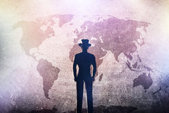 Silhouette of a man in hat standing in front of world map on grunge concrete wall Royalty Free Stock Photography