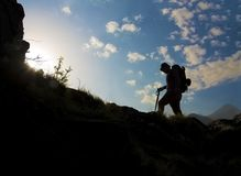Silhouette of a man hiking. In Himalayan mountains with backpack. Extreme mountainous terrain. Outdoors on a cloudy day blue sky Stock Photos
