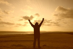 A silhouette of a man with his arms in the air Royalty Free Stock Images