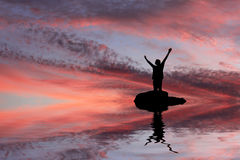 Silhouette of a man with his hands raised and his reflection Stock Image
