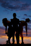 Silhouette man hold two women leaning back sunset. A silhouette of a men holding on to two women leaning back stock image