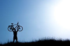 Silhouette of a man holding  bicycle on blue sky. Silhouette of  man holding  bicycle on blue sky Royalty Free Stock Photo