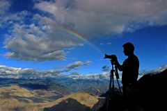 Silhouette of Man Holding Camera on Tripod With Mountain and Rainbow on Background Under Gray Clouds and Blue Sky at Daytime Royalty Free Stock Image