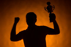 Silhouette of man holding champion cup. royalty free stock photos