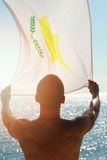 Silhouette of Man holding Cyprus flag in front of the sea Stock Images