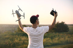Silhouette of man holding drone quad copter and remote control enjoying freedom, victory, success. Business concept Stock Images