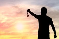 Silhouette of man holding Golden Medal. On sunset background, concept as winner and champion in sport and business Royalty Free Stock Image