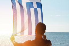 Silhouette of Man holding Greek flag. Man holding  flag of Greece in front of sea. Sunset colors Royalty Free Stock Image