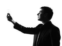 Silhouette  man  holding light bulb Royalty Free Stock Photos