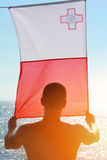 Silhouette of Man holding Malta flag in front of the sea. Sunset colors Royalty Free Stock Images