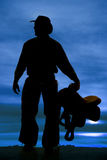 Silhouette man holding saddle look side. A silhouette of a cowboy holding on to his saddle Royalty Free Stock Photo