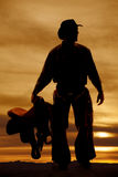 Silhouette man holding a saddle by side. A silhouette of a cowboy holding on to his saddle Royalty Free Stock Image