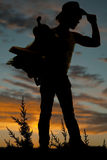Silhouette of a man holding a saddle and touching his hat Stock Photo