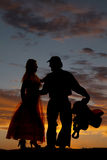 Silhouette man holding saddle with woman Royalty Free Stock Image