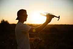 Silhouette of a man holding small compact drone and remote controller in his hands. Pilot launches quadcopter from his Stock Images