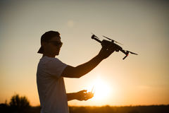 Silhouette of a man holding small compact drone and remote controller in his hands. Pilot launches quadcopter from his Stock Image