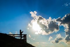 Silhouette of man holding smartphone and take a photo of sun and clouds with sky background. Silhouette of man holding smartphone and take a photo of sun and stock image