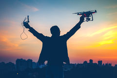 Silhouette of man holding switched on Drone. Quad copter and Remote control enjoying freedom, victory, success. Cityscape with dramatic colorful sunset sky in Royalty Free Stock Image