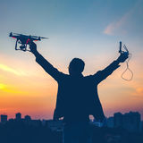 Silhouette of man holding switched on Drone. Quad copter and Remote control enjoying freedom, victory, success. Cityscape with dramatic sunset sky in the Royalty Free Stock Photo