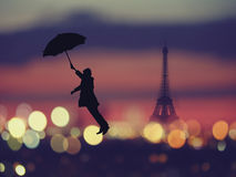 Silhouette of a man holding umbrella flying  over night Paris ,. France with eiffel tower on a background Royalty Free Stock Photos