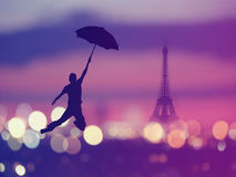 Silhouette of a man holding umbrella flying  over night Paris , Royalty Free Stock Photos