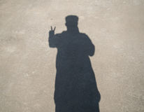 The silhouette of a man holding up two fingers to the ground Stock Photos