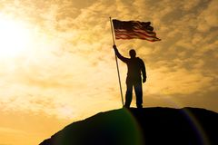 Silhouette of man holding US flag American on the mountain. The concept of Independence Day. a successful silhouette winner, a man waving an American flag on Royalty Free Stock Photography