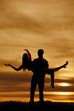 Silhouette of man holding woman with arms out Stock Image