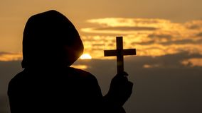 Silhouette of a man in a hood with a crucifix in his hand stock photography