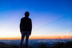 Silhouette of Man in hood standing on top of mountain waiting fo Stock Photos