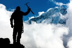 Silhouette of man with ice axe in hand and mountains Royalty Free Stock Image