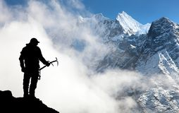 Silhouette of man with ice axe in hand and mountains Royalty Free Stock Images