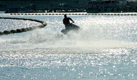 Silhouette of a man on the jet ski in the sea with water splashe Stock Images