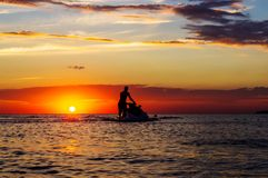Silhouette of a man on a jet ski in the sun. On the sea sunset in summer evening Royalty Free Stock Photos
